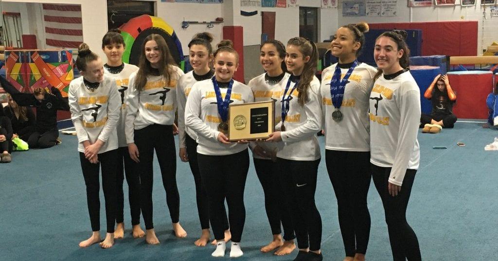 dynamic gymnastic gymnasts holding an award