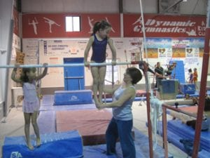 teodora training a gymnast on parallel-bars